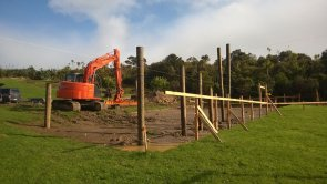 Hydraulic excavator prepares building platform after completion of geotech report confirms site suitability.