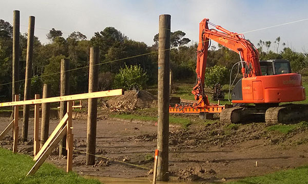 Hydraulic excavator prepares building platform after completion of geotech report.